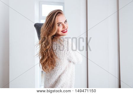 Happy young woman fighting with pillow at home