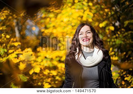 Portrait of a smiling young woman close up on a background of the autumn landscape and falling leaves