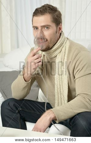 Portrait Of Man Inhaling Through Inhaler Mask