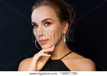 people, luxury, jewelry and fashion concept - beautiful woman in black wearing diamond earrings over dark background