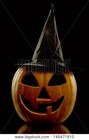 Scary Halloween pumpkin with hat on black background - decorations for Halloween holidays.