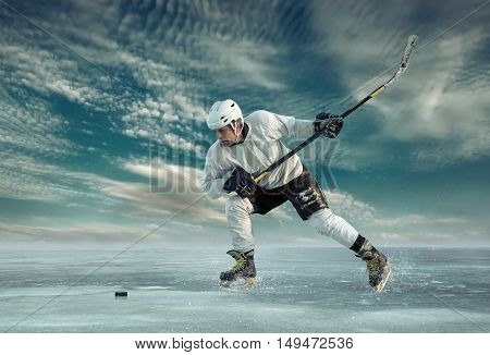 Ice hockey player in white in action outdoor under blue sky with clouds.