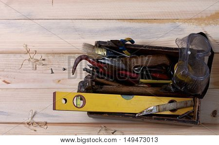 Set of old, rusty hand tools on the wooden background