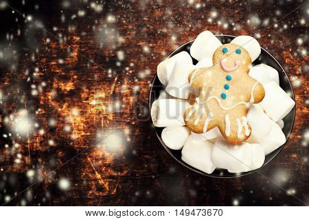Christmas greeting card with gingerbread man cookie and white marshmallow on wooden table with copy space for text. Christmas Composition with snowstorm