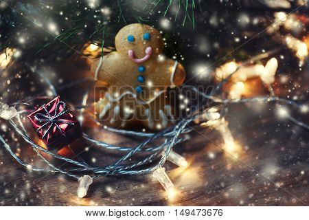 Christmas greeting card with festive lights garland decorations and homemade gingerbread man cookie on wooden table with copy space