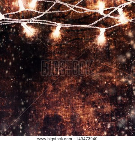 Beautiful abstract Christmas background with lights garland over wooden background with snowstorm