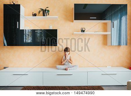 child doing yoga on the furniture. lotus.Yoga