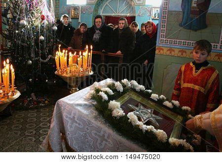 VOYUTYN UKRAINE - 08 JANUARY 2009: Ukrainian parishioners of the Orthodox Church light up candles during Christmas service.