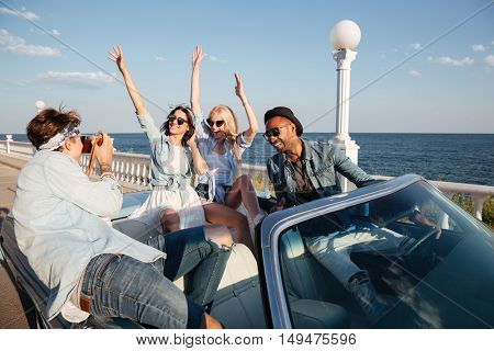 Group of cheerful young people driving and having fun in cabriolet
