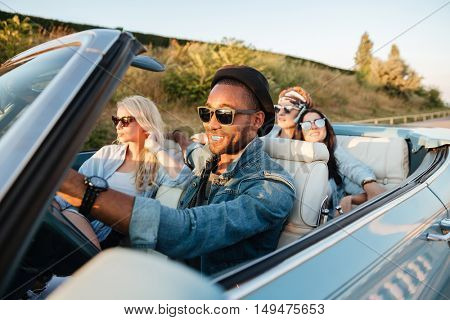 Group of happy young friends driving car in summer