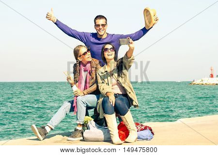 Cheerful friends having fun taking selfie with mobile at pier - Happy students smiling at camera for holiday photo on ocean background - Concept of teenager joyful moment outdoor - Vintage filter look