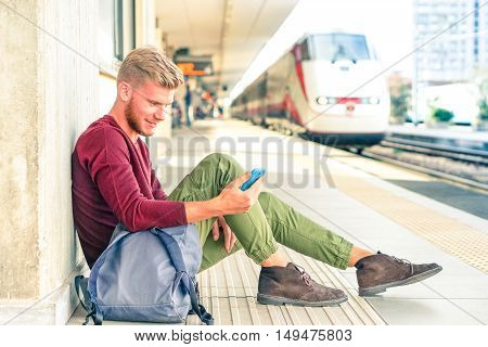 Portrait of young hipster man waiting train in railway station looking down at phone - Handsome guy sitting on platform using mobile locomotive arrival background - Concept of green public transport