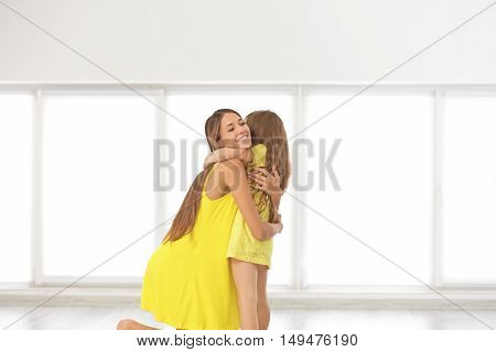 Cute girl with mother on light window background