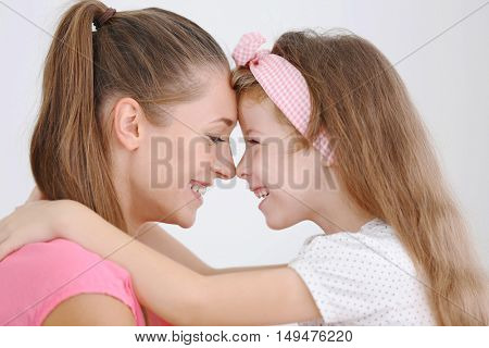 Cute girl with mother on light background