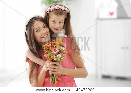 Greetings from daughter with flowers. Mothers day concept