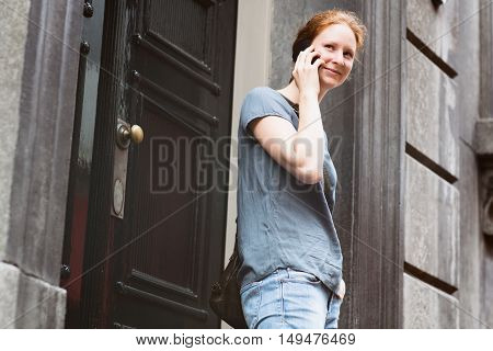 Woman On The Phone Before A Building