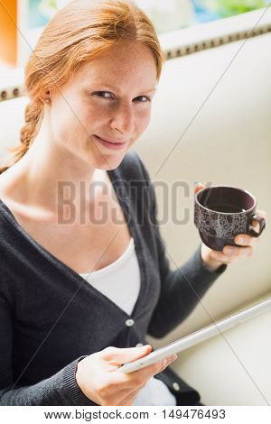 A young redhead woman with a tablet and a cup of tea smiles at the camera.