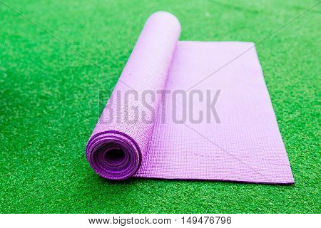 Pink Yoga Mat on a green Background. Health lifestyle concept.