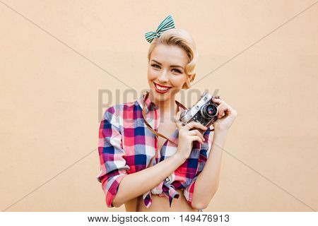 Happy smiling pinup girl in yellow dress using vintage camera and taking pictures over pink background