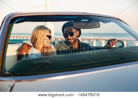 Portrait of multiethnic happy young couple in car in summer