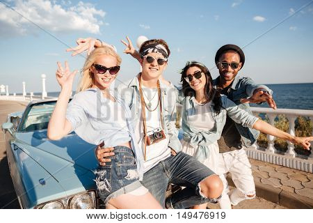 Multiethnic group of cheerful young people standing and showing peace sign near vintage car in summer