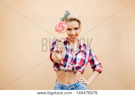 Smiling charming pin-up girl standing and showing sweet lollipop over pink background
