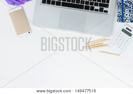 Laptop keyboard and phone on white table mock up flat lay scene, copy space on white table