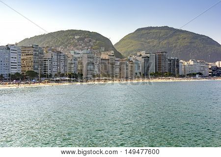 Small part of the Copacabana beach in Rio de Janeiro with its buildings around and in the background on the hill the Cantagalo slum.