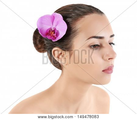 Portrait of young attractive woman with exotic flower in hair on white background