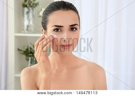 Portrait of young woman applying facial cream