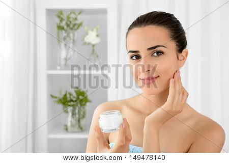Portrait of young woman holding facial cream