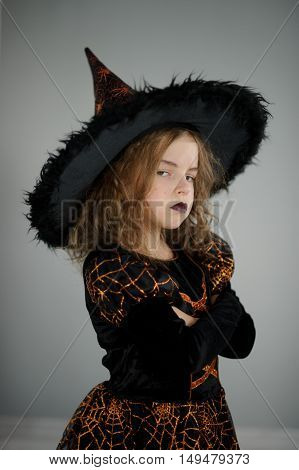 All Hallows Eve. Beautiful girl 8-9 years in image the evil sorcerer. She is dressed in black and orange dress and a big hat. Girl tries to make an evil look. Trick or Treat. Children adore Halloween