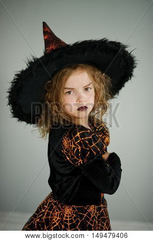 Preparation for Halloween. Cute girl 8-9 years in image the evil fairy. She is dressed in black and orange dress and a big hat. From under a hat a wild hair sticks out. Children adore Halloween