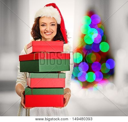 Beautiful happy woman with Christmas gifts on blurred interior background. Christmas holiday concept.