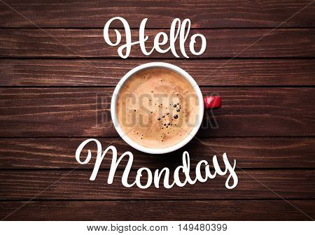 Text HELLO MONDAY and cup of aromatic coffee on wooden background, closeup