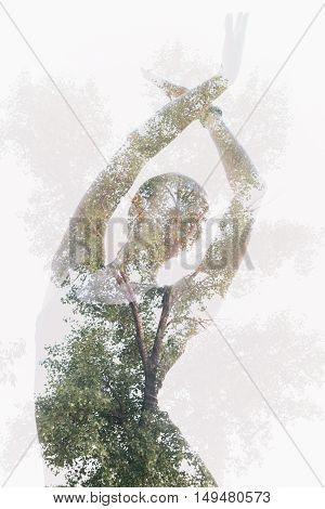 Double exposure portrait of dancing woman combined with photograph of tree