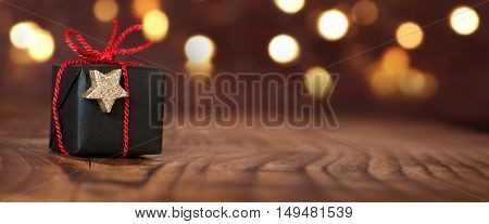 Christmas gift with red loop in front of a dark background with lights