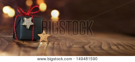 Christmas gift and stars on an empty table with bokeh