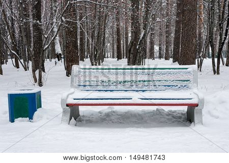 A bench in winter park after snowfall. Nobody.