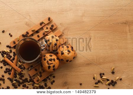 Fresh, just baked cupcakes with chocolate, cinnamon and coffee seeds set with cup of dark coffee on a wooden table. Muffins with cup of americano and cardamom.