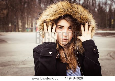 Portrait of a teenage girl outdoor wearing winter coat with the faux - fur hood on
