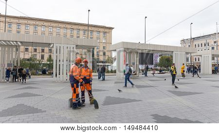 Moscow - September 10 2016: Mayakovsky Square in the city center the cleaners talking and people walk and ride on a swing September 10 2016 Moscow Russia