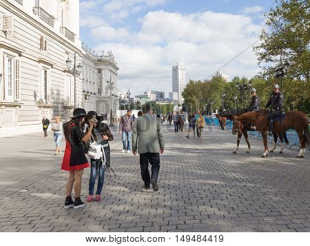 Madrid - 7 October 2015: Tourists walk around and take pictures of the Royal Palace and the policemen on horses follow the order of 7 October 2016 Madrid Spain