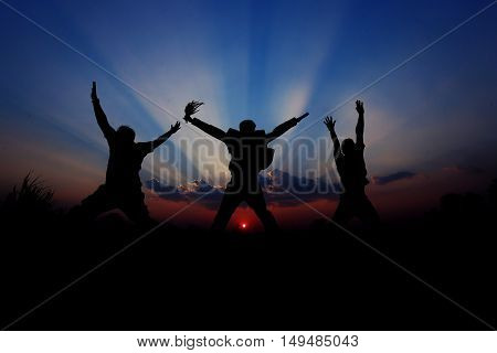 Silhouette of three man jumping happy time