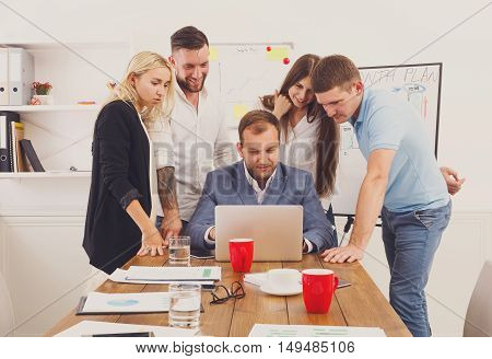Happy business team, work result. People laugh near laptop in the office. Successful corporate group of female and male coworkers look at corporate internet site together at work