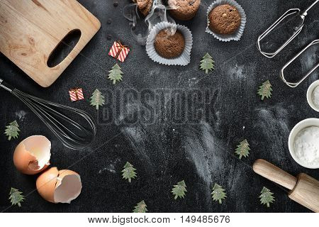 Kitchen utensils and christmas toys on black background copy-space.