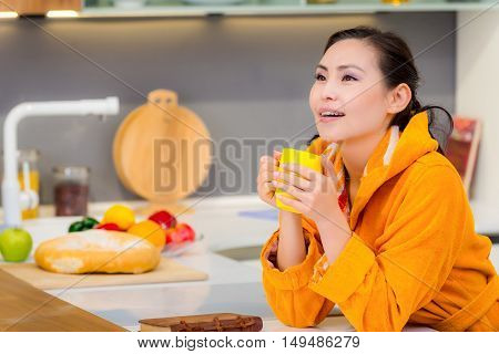 Young beautiful asian female drinking tea or coffee in the morning