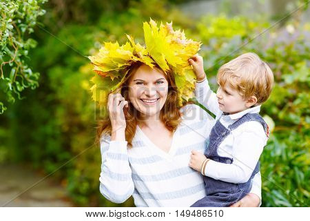 Young mother with a maple leaf wreath holding little toddler kid boy in autumn park. Happy family, woman and son hugging on sunny fall day outdoors.