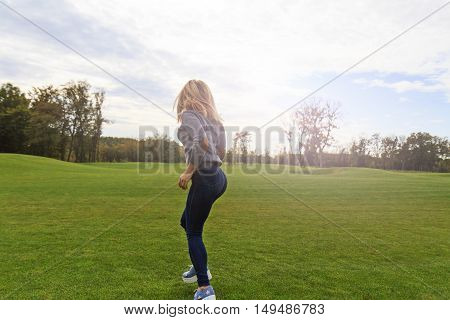 Blonde girl jumping with joy on a background of green lawn mood, emotion, smile with sunny hotspot