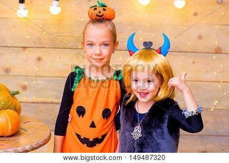 Happy group of children during Halloween party playing around the table with pumpkins